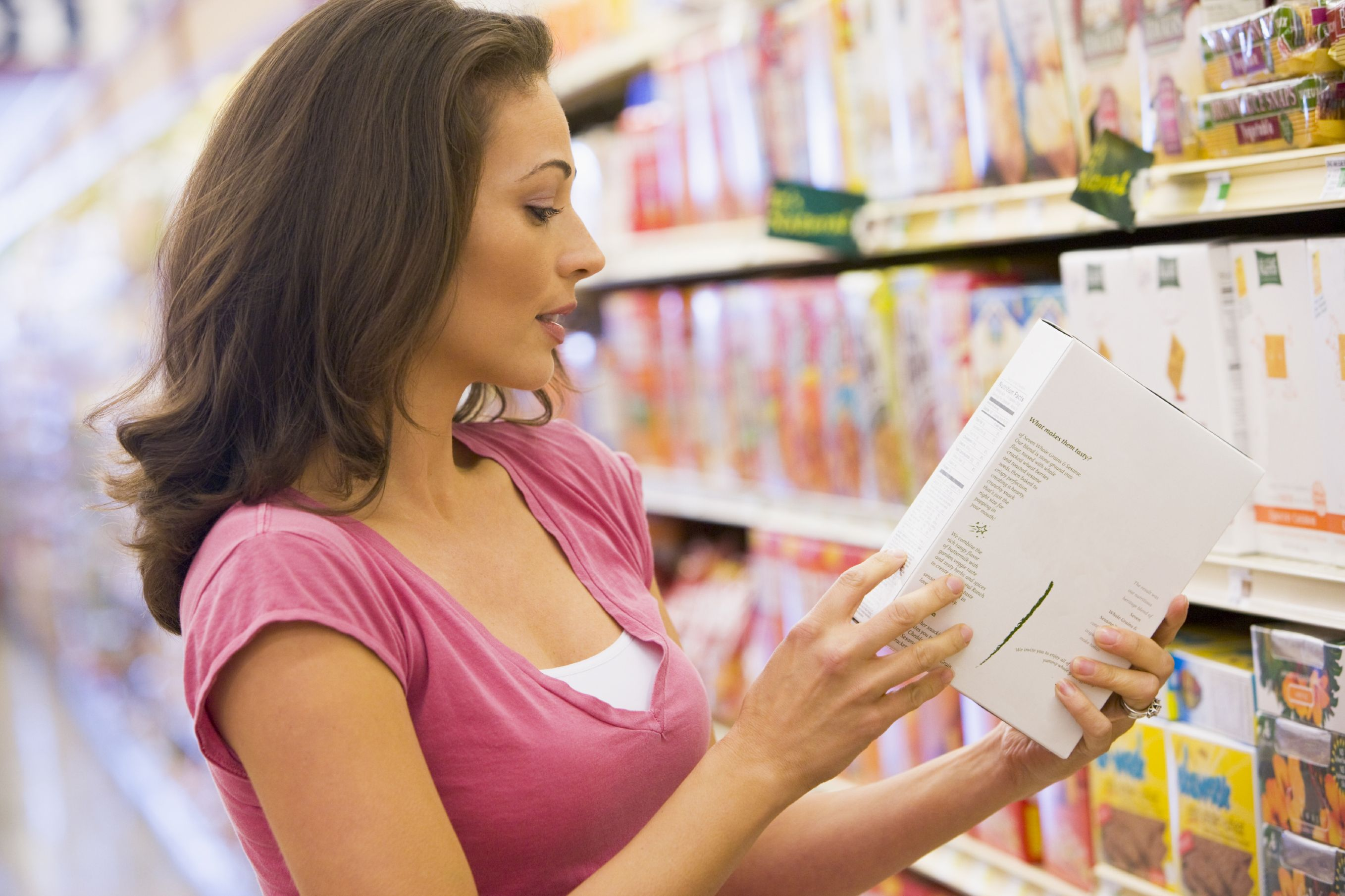 Woman checking food labelling in supermarket